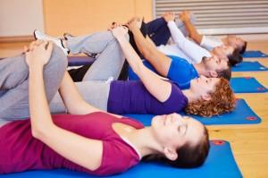 Gruppe macht Dehnübungen im Fitnesscenter